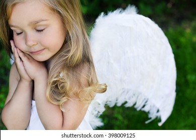Girl in angel's costume prays