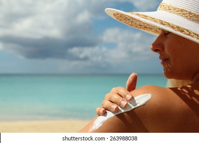 girl aplying  sun protection cream on the beach