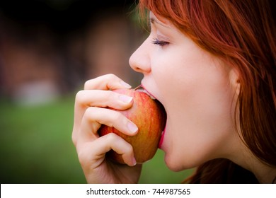 Girl with apple in the garden
