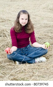 Girl with an apple on dry  grass