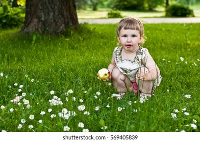 Girl with apple sitting on the grass in park