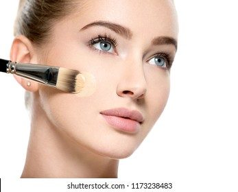 Girl applies  tonal foundation on face use makeup brush. Woman makes makeup.