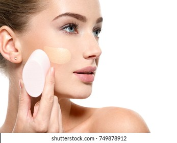 Girl applies  tonal foundation  on the face use sponge. Woman makes makeup.