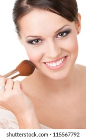 Girl applying cosmetics to her face with the help of cosmetic brush, isolated on white