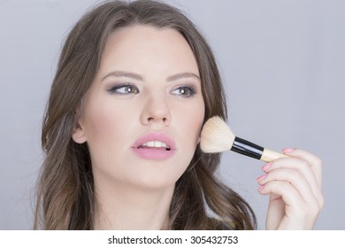 Girl applying makeup with a makeup brush