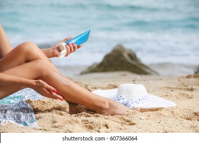 Girl applying sunscreen on her legs