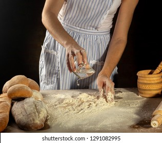 the girl in the apron pours water from the cup for to knead the