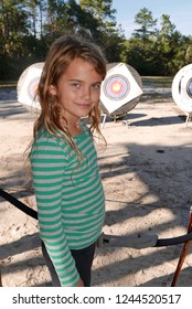 Girl at an archery range, holding a bow and smiling at the camera