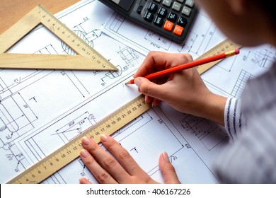 Girl architect draws a plan, graph, design, geometric shapes by pencil on large sheet of paper at office desk. Soft focus