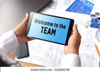 A girl (architect, student, businesswoman) at a table with business accessories, accessories for drawing (plans, rulers) and training with tablet with text Welcome to the team
