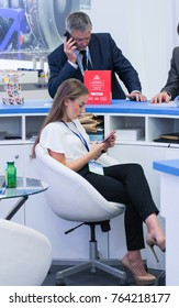 Girl in armchair with phone. St. Petersburg, Russia - 3 October, 2017. Young girls and women at the St. Petersburg gas forum.
