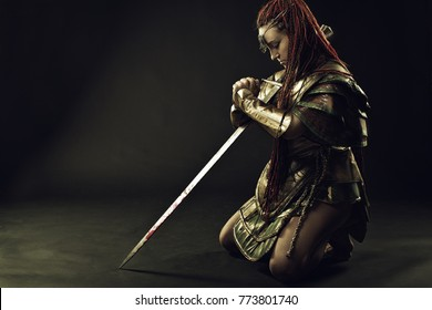 Girl in armor standing on her knees  with sword