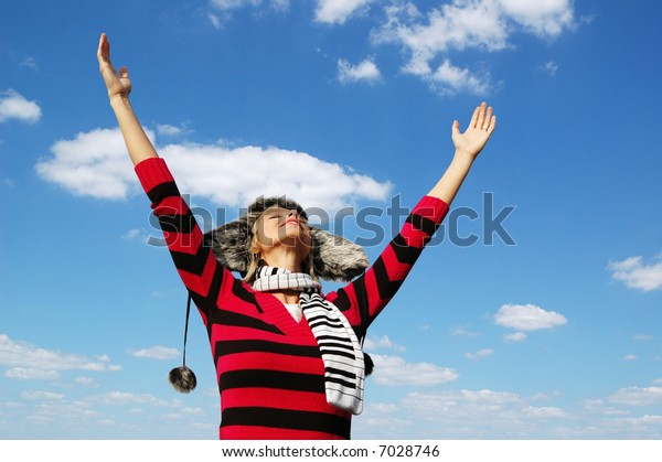 Girl with arms wide open in attitude of worship