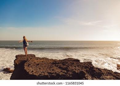 Girl with arms wide open enjoying sea / ocean scenery.