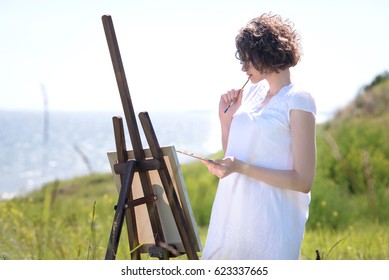 The girl is an artist with his easel on the banks