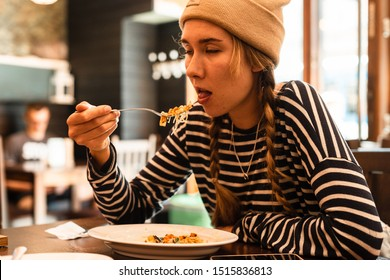 Girl in the Asian fst food cafe getting lunch. Woman eating Asian food.