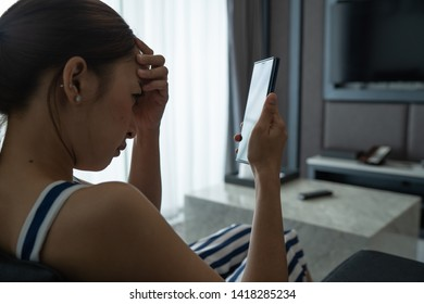 girl asian in sad emotional by use smartphone in room her by relaxing on vacation with sit on sofa
