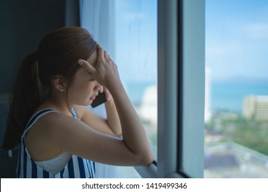 girl asian in sad emotional by use smartphone in room her by relaxing on vacation with serious talk beside windows