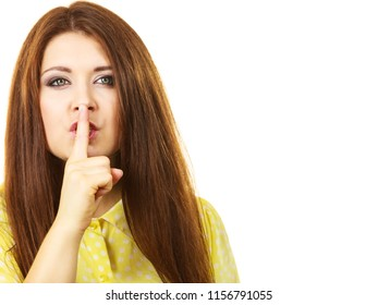 Girl asking for silence or secrecy with finger on lips, hush hand gesture, on white, copy space text area