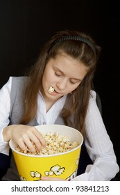 girl asleep in a movie theater with popcorn