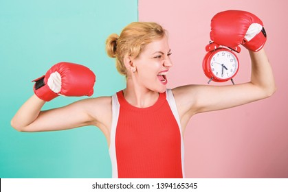 Girl athlete boxing gloves and alarm clock. Sport lifestyle and healthy regime. Habits and regime concept. Improve yourself. Overcome harmful habits. Time for training. Get used to personal regime.