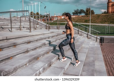 Girl athlete, goes steps, walk free space, fitness workout, summer in city, day and morning. Sportswear, smartphone headphones. Active lifestyle, motivation power. Internet application music