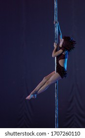 Girl athlete gymnast shows an acrobatic performance on a pylon.