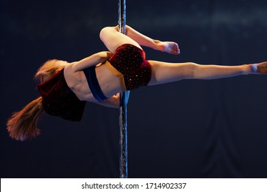 Girl athlete gymnast shows an acrobatic performance on a pylon.