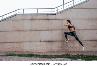 The girl athlete jumps, runs for a morning jog. In the summer in the city. The concept of a healthy lifestyle. View from the side against the background of the concrete wall. Free space for text.