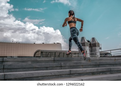 The girl athlete jumps up stairs, runs for a morning jog. In summer in city. The concept of healthy lifestyle. View from rear on a background of blue sky and concrete stairs. Free space for text.