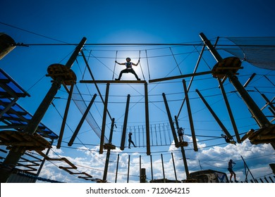 The girl athlete overcoming obstacles in the rope Park. Girl on top, against the sky and the sun