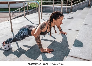 Girl athlete pressed on the stairs in the morning in the city. Makes warm-up gymnastics. The concept of a healthy lifestyle. In sportswear and sneakers. Tanned skin and tattoos.