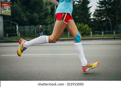 girl athlete running a marathon on a city street, feet knees in blue kinesiology taping