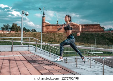 Girl athlete runs in the city on the stairs, summer day. In his hand, the player listens to music on headphones. Sports and healthy lifestyle. Free space for text.