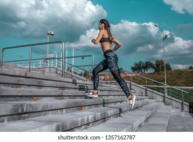 Girl athlete runs down the stairs in the summer in the city In headphones, sportswear leggings top. Free space. Concept motivation, active life position, healthy lifestyle. Free space for text.