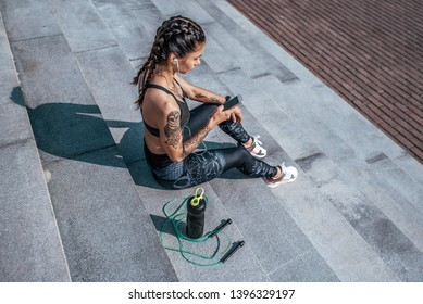 Girl athlete sitting steps resting after workout fitness summer city, day morning. Sportswear, smart phone, headphones, jumper. Active lifestyle motivation power. Internet application, music.
