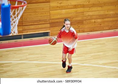 Girl athlete in sport uniform playing basketball