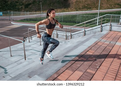 Girl athlete woman, runs stairs, summer city, free space, fitness workout, day morning. Sportswear top sneakers. Active lifestyle, motivation power. Endurance achievement success muscles competitions