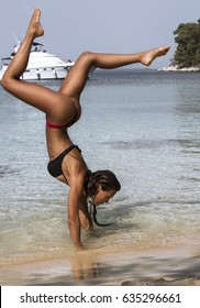 Girl with attractive tan body doing hand stand in shallow water on exotic beach