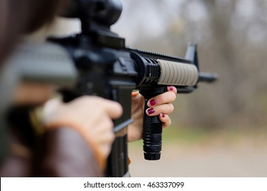 a girl with an automatic weapon, looks through the scope, close-up weapons