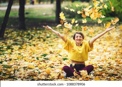 girl in autumn sits on grass and cheerfully casts up yellow leaves. Life style