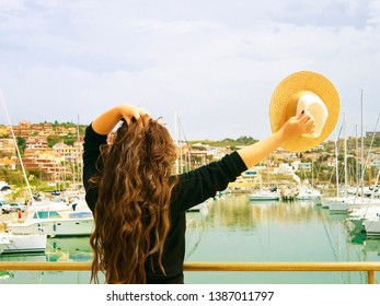Girl with awesome long hair and hat in the hand on sea port with yachts. Turism agency concept. Tour sale. Lifestyle blogger and traveler. Summer vibe