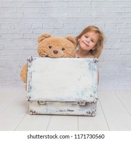 girl, baby in dress on white brick wall background with suitcase, with toy bear