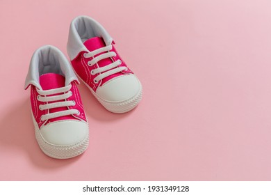 Its a girl, Baby sport shoes on pastel pink color background. Kid small size sneakers, canvas booties closeup view. Space, card invitation template