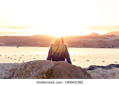 girl back to camera enjoy by beautiful sunset above Israeli city Eilat and desert mountains scenic landscape