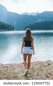 girl in back standing in white shorts against a black lake
