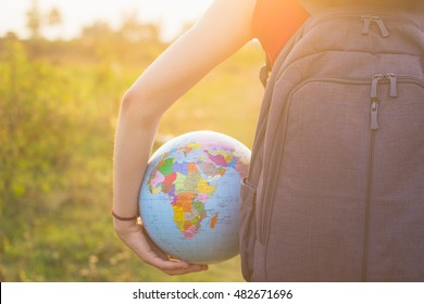 A girl with backback holding globe in sunset light background
