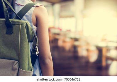 Girl with backpack entering to the classroom. Education concept.
