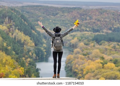 Girl with a backpack and a hat standing on a hill. Hands raised up. River and mountains below. Back view