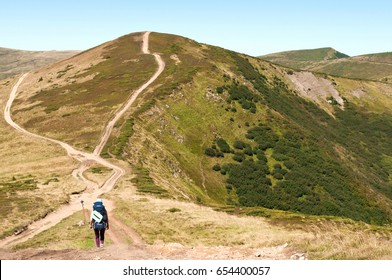 A girl with a backpack heading to a road fork before a mountain hill. The Carpathian mountains in late summer. Svydovets ridge
